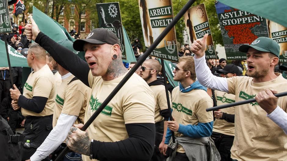 """Durchtrainierte und tätowierte Männer demonstrieren in einheitlichen T-Shirts der Partei """"Der 3. Weg"""" in Plauen"""