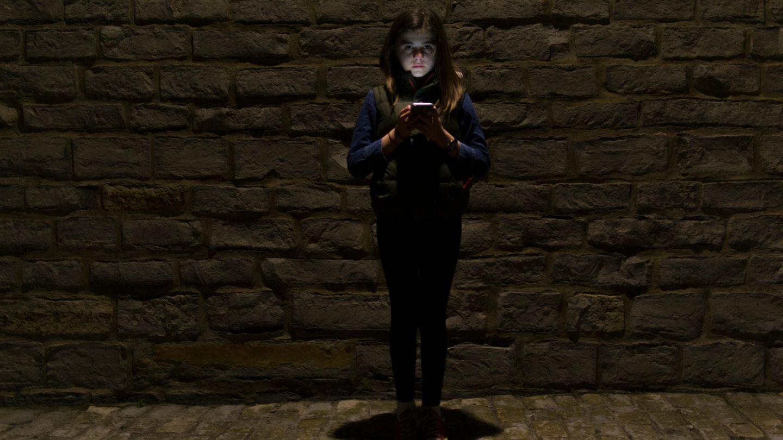Mädchen im Dunkeln mit Smartphone