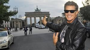 David Hasselhoff trägt lächelnd eine Sonnenbrille und zeigt auf das Brandenburger Tor