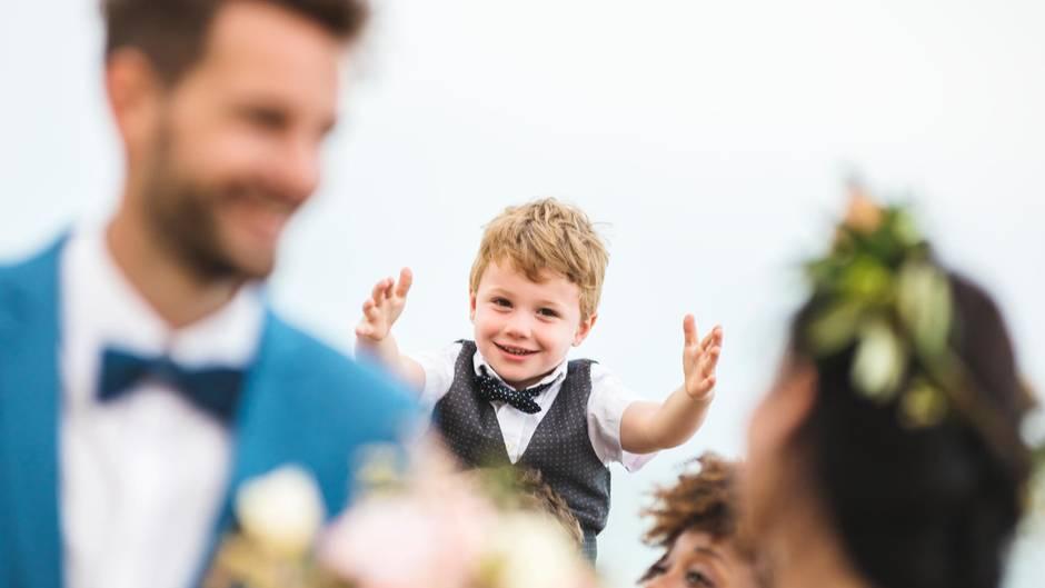 Ein kleiner Junge strahlt eine Braut an