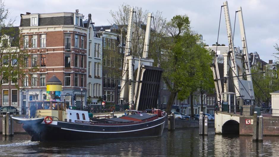 Ein Hausboot fährt durch einehochgezogene Zugbrücke (Symbolbild)