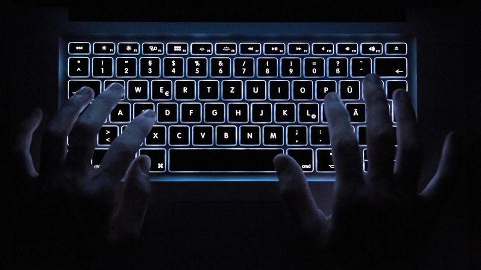 Finger schreiben auf einer leuchtenden Tastatur im Dunkeln