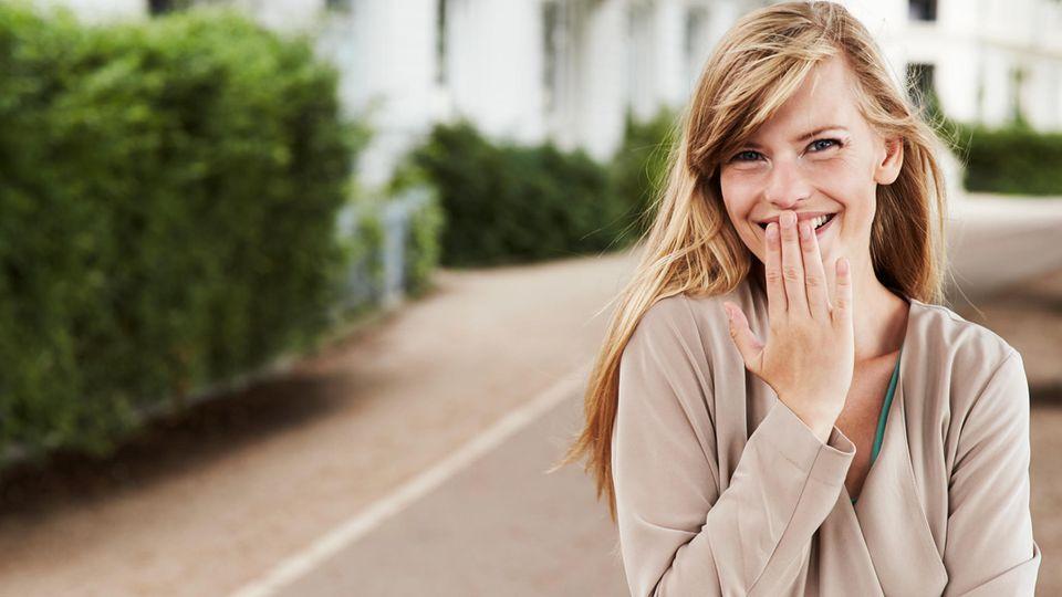 Eine junge Frau lacht und hält sich dabei die Hand vor den Mund