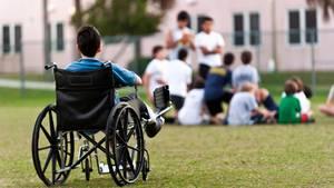 Eine Junge sitzt im Rollstuhl, auscgeschlossen aus einer Gruppe Jugendlicher