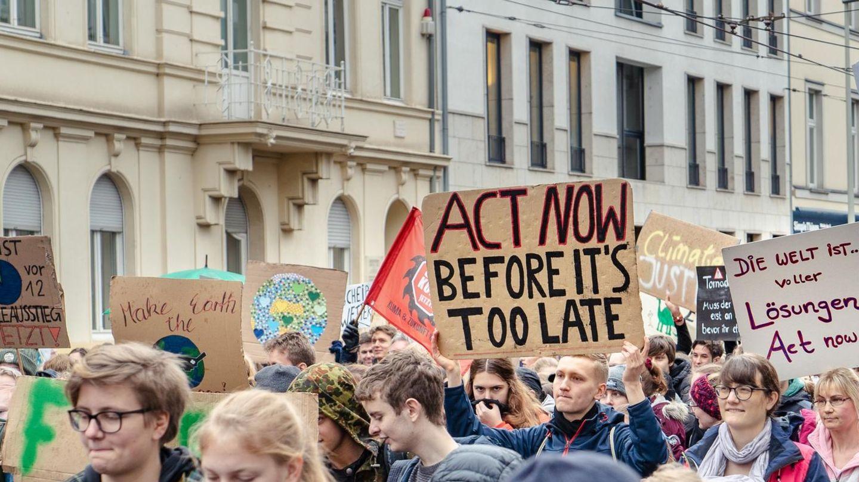 """Auf Demo gegen den Klimawandel hält ein Mann ein Schild mit der Aufschrift """"Act now before it's too late""""."""