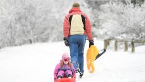 Ein Mädchen lässt sich amSamstagauf dem verschneiten Plateau des Großen Feldbergs in Hessen auf einem Schlitten ziehen