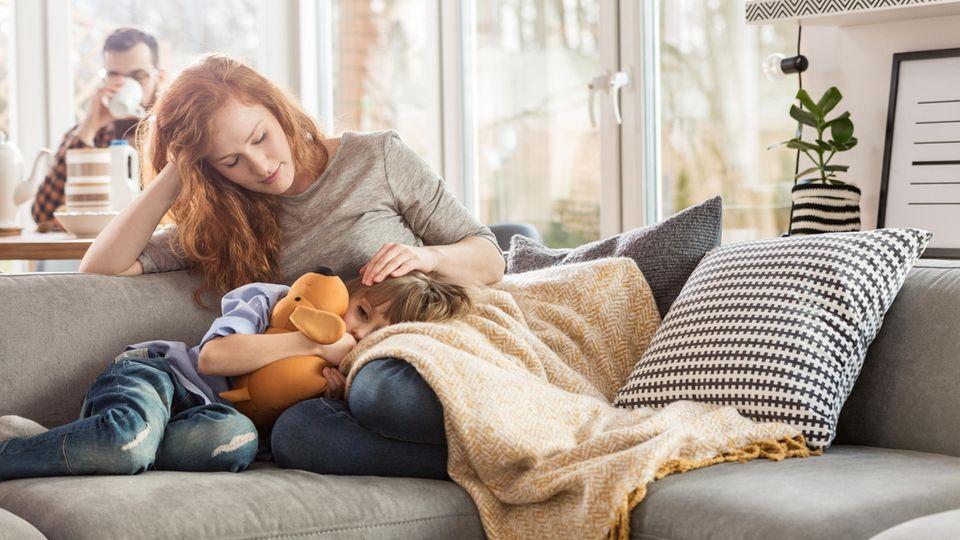 Mutter sitzt mit krankem Kind auf Sofa