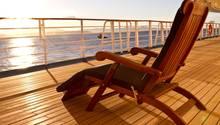 Ein Liegestuhl steht an Deck eines Kreuzfahrtschiffes