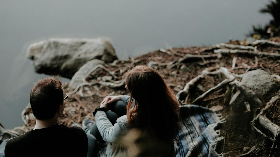 Pärchen sitzt am Fluss