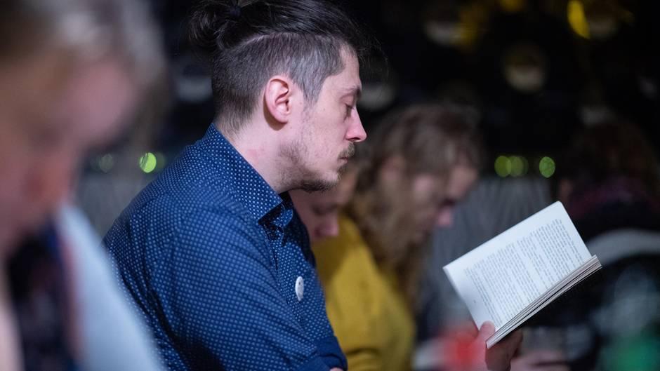 Ein Mann im blauen Hemd hät ein aufgeschlagenes Buch vor sich und liest