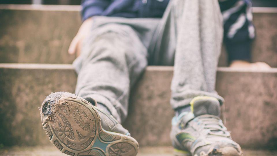 Ein Junge mit kaputten Turnschuhen