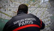 """Ein Feuerwehrmann in dunkelblauer Jacke mit """"Sapeurs Pompiers Paris"""" auf dem Rücken betrachtet einen Stadtplan von Paris"""