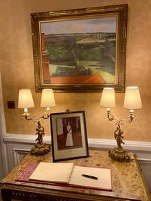 Im Foyer der Residenz liegt auf einem Tisch vor dem Portrait von Elisabeth II. das Gästebuch aus, in das Charles und Camilla sich nach ihrer Ankunft eintragen werden.