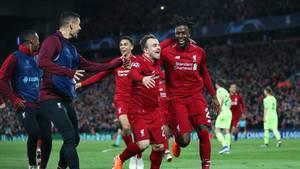 Drei Spieler in Trikots des FC Liverpool laufen jubelnd auf zwei Spieler in Trainingsanzügen zu