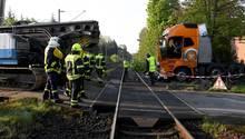Ein mit einer Ramme beladener Sattelzug steht nach der Kollision mit einem Zug auf einem Bahnübergang