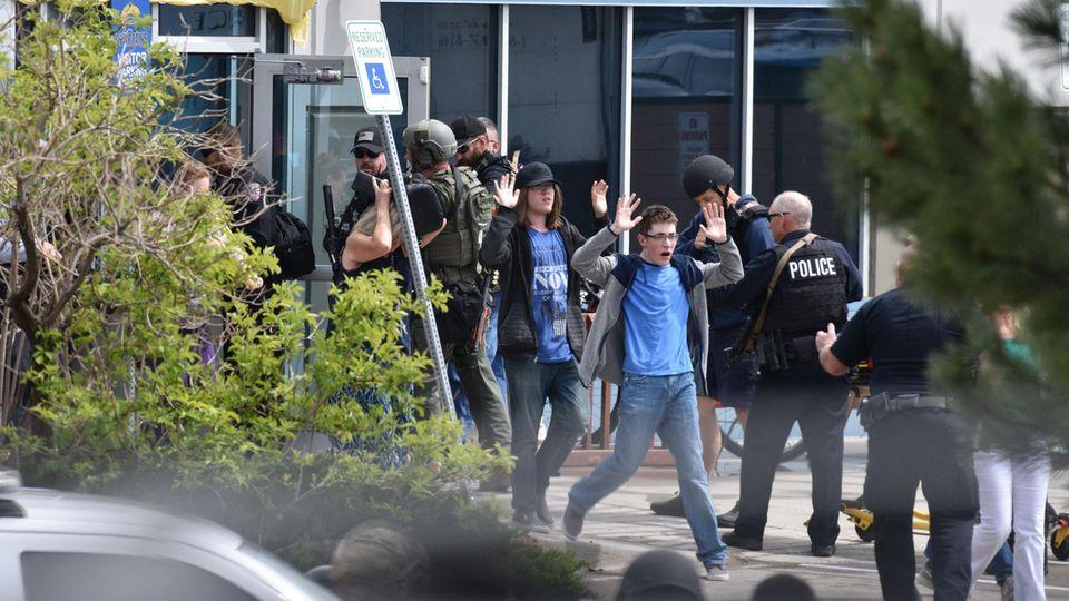 Zwischen Polizisten in schwerer Schutzkleidung laufen Schüler mit erhobenen Händen aus einem Gebäude