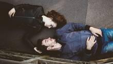 Liebespaar liegt auf dem Boden und guckt sich in die Augen