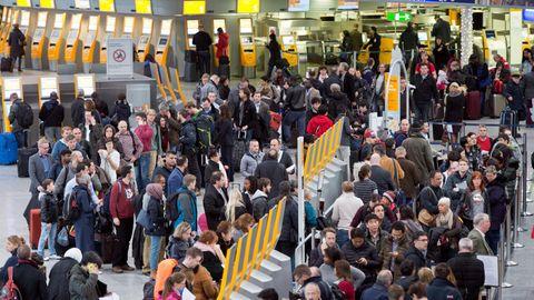 Passagiere warten auf dem Frankfurter Flughafen an Check-in-Schaltern