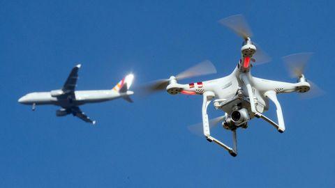 In der Umgebung eines deutschen Flughafens: Eine private Drohne fliegt in knapp zehnMetern Flughöhe über einem Garten, als in weiter Entfernung ein Flugzeug zu sehen ist.