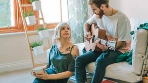 Ein junges Paar, der Mann spielt Gitarre