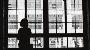 Einsamkeit: Frau steht vor einem großen Fenster.