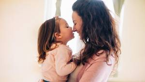 Eine junge Mutter hält ihre Tochter auf dem Arm. Das Kind küsst ihr auf die Nase, die Mutter lacht.