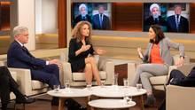 Auf hellen Sesseln sitzen ein grauhaariger Mann im Anzug, eine Frau mit dunkelblonden Locken und eine Frau mit schwarzen Haaren