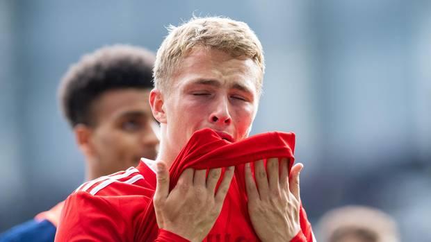 HSV-Spieler Jann-Fiete Arp zieht den Saum seines roten HSV-Trikots mit beiden Händen zum Gesicht
