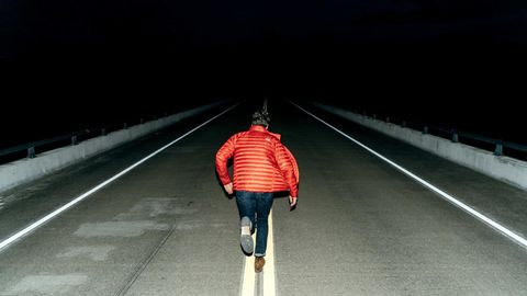 Mann läuft auf dunkler Straße