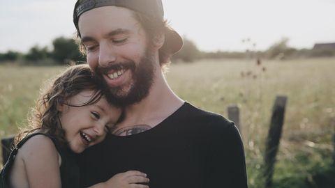 Vater mit seiner Tochter auf dem Arm auf einer Wiese