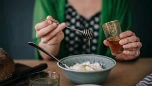 Frau tut Honig auf ihr Müsli