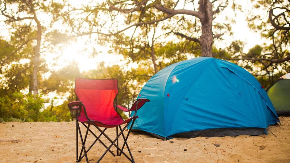 Roter Campingstuhl und blaues Zelt im Wald.