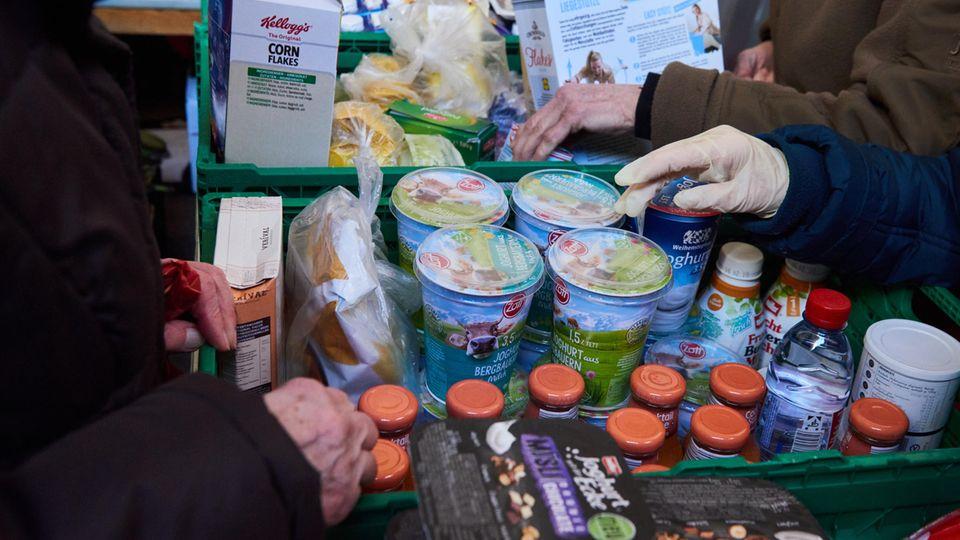 Hände fassen nach abgepacktem Joghurt, Soßen und Cornflakes in Körben der Berliner Tafel