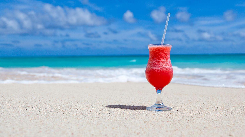 Ein Cocktailglas steht an einem weißen Sandstrand