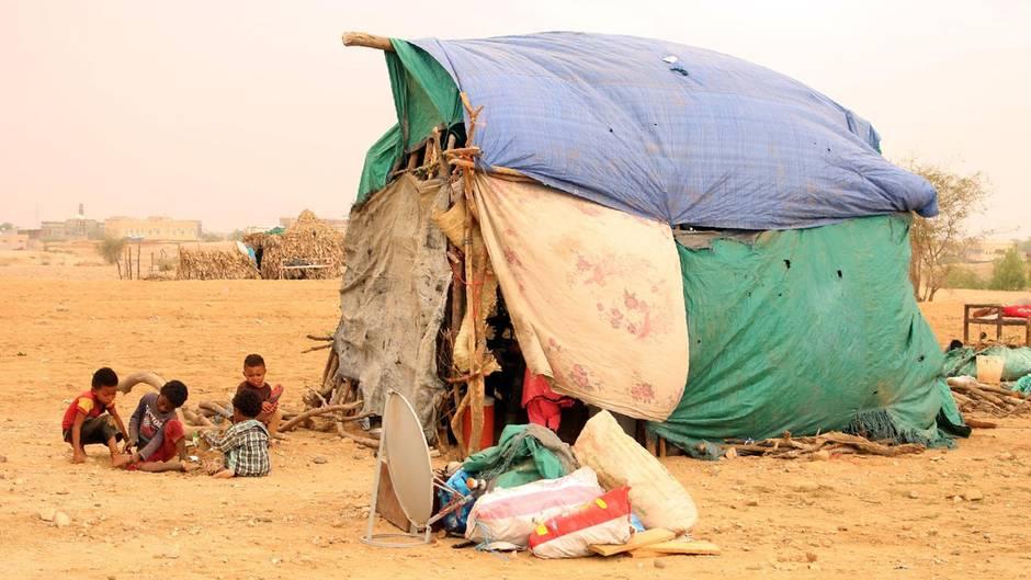 Flüchtlingskinder im Jemen spielen vor einem provisorischen Zelt aus rissigen Planen