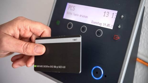 Arbeitszeiterfassung. Ein Mitarbeiter erfasst seine Arbeitszeit digital an einem Terminal.