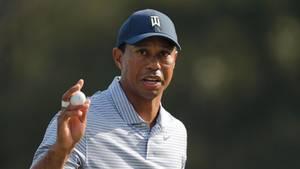 Golf-Profi Tiger Woods steht auf einem Golfplatz und hält mit der rechten Hand einen Golfball hoch