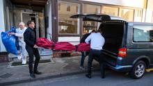 Bestatter schieben im niedersächsischen Wittingen einen Leichensack in einen Leichenwagen