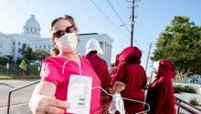 """Eine Frau in pinker Klinik-Kleidung hält einen Draht-Kleiderbügel als Werkzeug für eine """"Heim-Abtreibung"""" in der rechten Hand"""