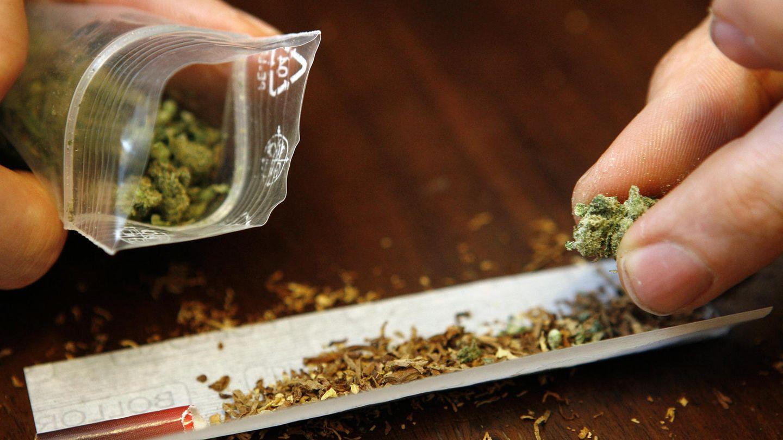 Ein Joint wird gedreht. Daneben wird eine kleine Tüte mit geringer Menge von Marihuana gehalten.