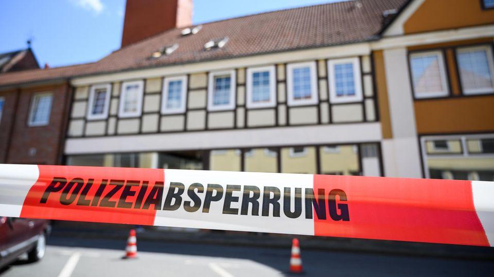 """Hinter Flatterband mit """"Polizeiabsperrung"""" steht ein hellgelbes Fachwerkhaus"""