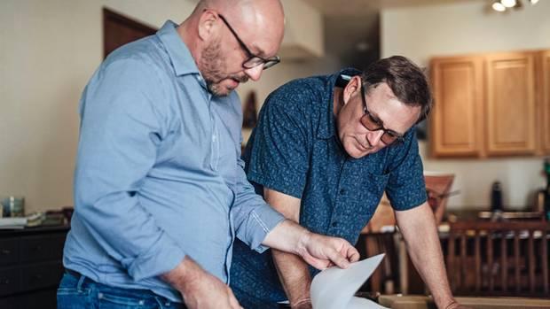 Tim zeigt Chris Einreisedokumente und Zeugnisse ihres Vaters.