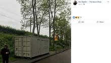 Ein Mann steht neben einem am Straßenrand stehenden Container