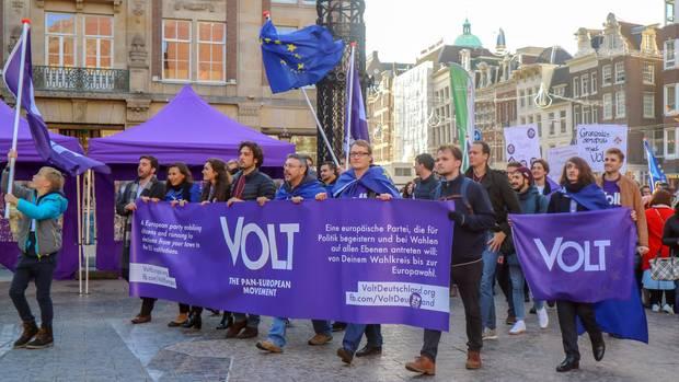 """Mitglieder der Europa-Partei """"Volt"""" ziehen mit Flaggen und Bannern in Amsterdam durch eine Straße."""