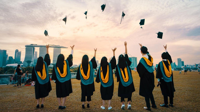 Sieben Mädchen vor Stadtkulisse werfen ihre Talare in die Luft.