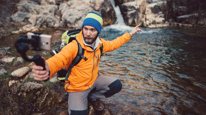 Ein Wanderer filmt sich selbst vor einem Wasserfall