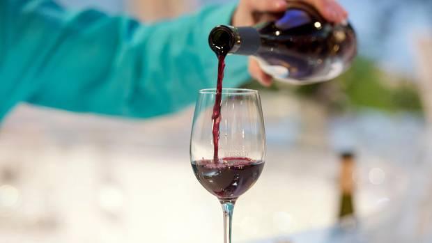 Ein Mann schenkt Rotwein in ein Weinglas