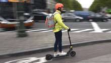 Ein Frau fährt mit einem E-Roller auf einem Fahrradweg in Brüssel.In vielen europäischen Metropolen sind E-Scooter schon im Einsatz. In Deutschland entscheidet jetzt der Bundesrat über ihre Zulassung.