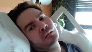 Eine Mann Ende 30 liegt in einem Krankenhausbett. Sein Kopf mit braunem Haar ist in die Kamera gedreht