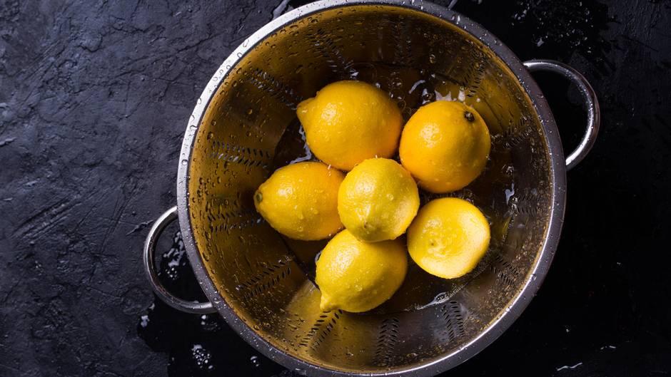 """Zitronen sollten - wie jedes Obst und Gemüse -gewaschen werden. """"Anhaftender Schmutz, Staub oder Keime können beim Anschneiden über das Messer einen Teil dessen, was außen auf der Schale sitzt mit ins Innere der Frucht tragen"""", schreibt dazu die Verbraucherzentrale. Die Zitrusfrüchte spülen Sie am besten mit warmen Wasser ab und rubbeln sie im Anschluss trocken. Dafür eignet sich ein sauberes Küchentuch oder Küchenkrepp.  Auch Bio-Zitronen sollten vor dem Anschneiden gründlich gewaschen werden. Der Anbau von Bio-Zitronen ist streng geregelt - unter anderem ist der Einsatz von Pflanzenschutzmitteln und Konservierungsstoffen verboten. Nach dem Waschen darf die Schale daher bedenkenlos zum Kochen oder Backen verwendet werden."""